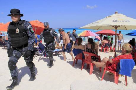 Mexican Police agents patrol amongs the tourists at a beach ...